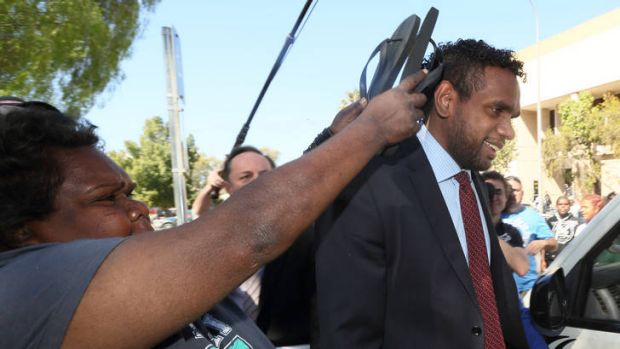 A family member tries to shelter Liam Jurrah as he leaves court in Alice Springs yesterday.