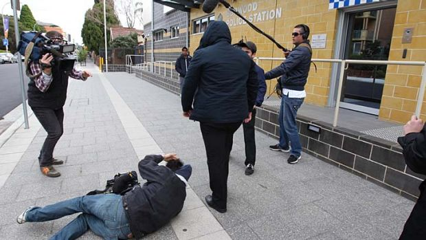 Violence … the injured cameraman, on the ground after he was shoulder charged outside court.