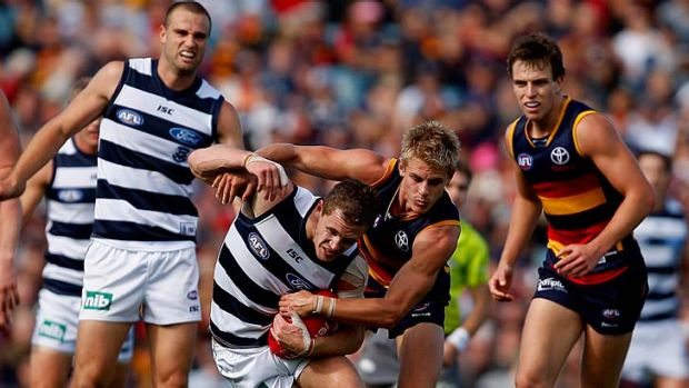 David Mackay of the Crows puts the squeeze on Joel Selwood of the Cats when the teams met in round seven.