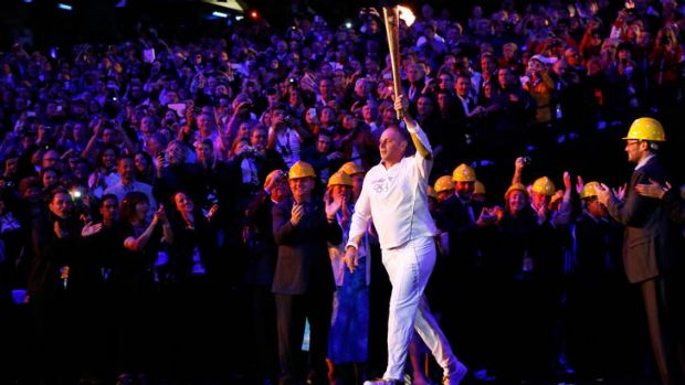 Voice of experience ... Torchbearer Steve Redgrave carries the Olympic flame into the stadium.