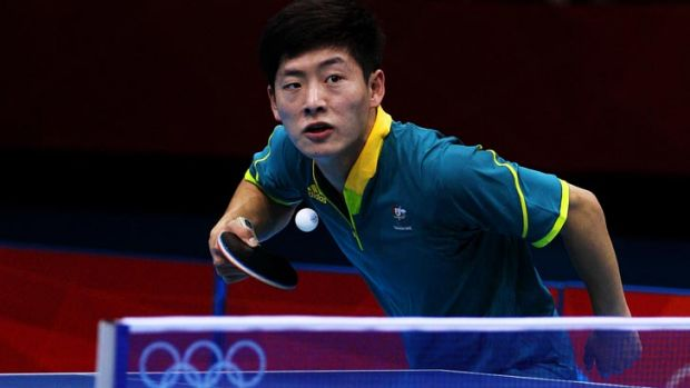 Justin Han of Australia serves against Mawussi Agbetoglo of Togo during their men's singles preliminary round match on ...