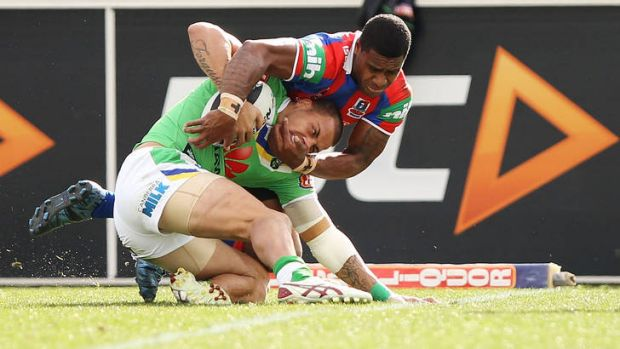 Kevin Naiqama of the Knights attempts to pull Blake Ferguson of the Raiders over the try line.