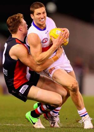 Leashed: Bulldog Matthew Boyd is stopped in a tackle by St Kilda's Brendon Goddard.