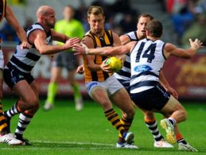 Hawthorn's Sam Mitchell finds himself surrounded by Geelong's Paul Chapman, James Kelly and Joel Selwood when the teams ...