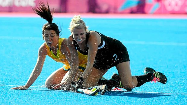 New Zealand's Emily Naylor battles with Australia's Jade Close in their Olympic hockey pool match.