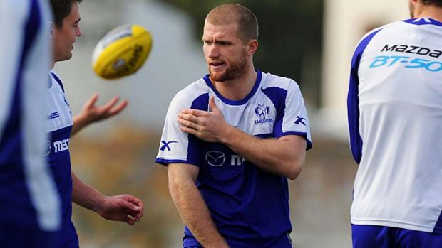 North Melbourne's Leigh Adams holds his shoulder during training.