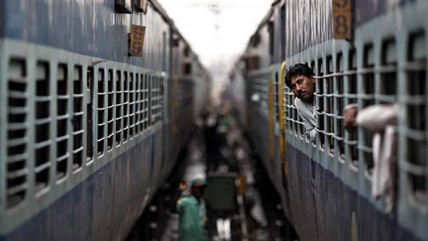 World's largest power shortage ... a passenger looks through the window of a train as he waits for electricity to be ...