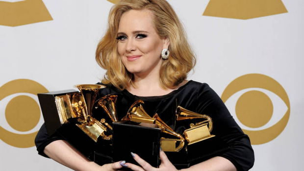 Adele poses backstage with her six awards at the 54th annual Grammy Awards.
