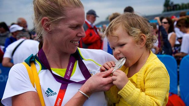 Sarah Tait shows her daughter Leila her silver medal after winning at Eton Dorney.