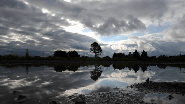 Rain clouds loom reflected in the water at the Jerrabomberra Wetlands car park.