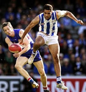 Coming through: North Melbourne's Daniel Wells leads Robert Murphy to the ball.
