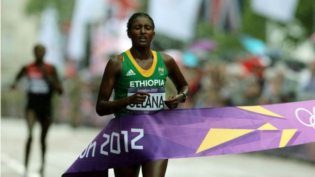 An exhausted Tiki Gelana of Ethiopia crosses the finish line to win the women's marathon.