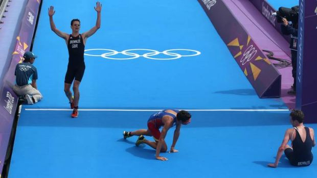 The arrival ... Jonathan Brownlee crosses the finishing line to win bronze. On the ground are silver medallist Javier ...