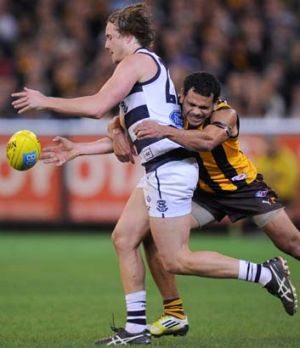 Mitch Duncan is tackled by Hawthorn's Cyril Rioli.
