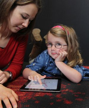 Coco Maslin, 4, with researcher Leila Dafner, loves colouring in pictures on her iPad.