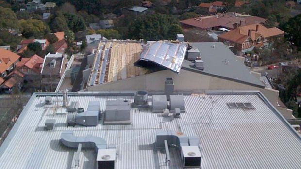 The roof of an office block in North Sydney is blown off during today's strong winds.