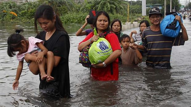 Residents wade in waist-deep floodwaters in order to get to their submerged shanties in Valenzuela, north of Manila .