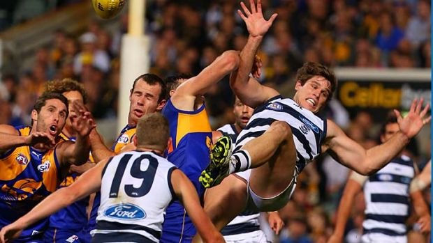 Tom Hawkins of the Cats is about to be concussed after crashing to the ground following a marking contest in the first ...