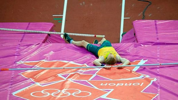 Steve Hooker lies on the mat after bombing out of the pole vault final without registering a height at the London Olympics.