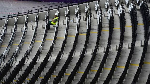 A worker takes a break during the clean-up operation at the London 2012 Olympic stadium.