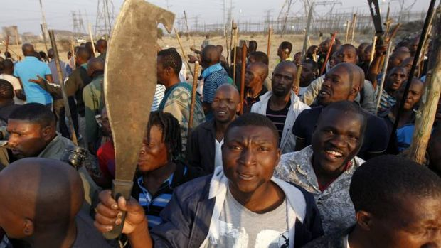 Thousands of striking miners armed with machetes and sticks faced off with South African police at Lonmin's Marikana mine.