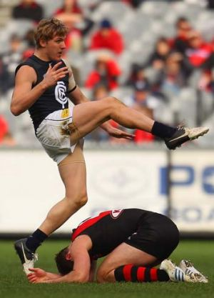 Down and out: Carlton's Tom Bell takes his kick over the back of Bomber Jobe Watson.