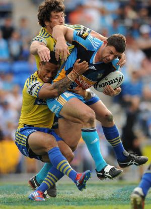 Mark Minichiello of the Titans is tackled by two Eels players.