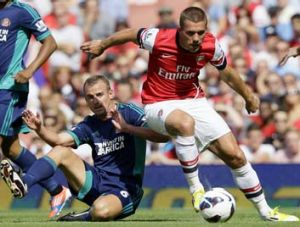 Modest debut ... Arsenal's Lukas Podolski outmanoeuvres Sunderland's Lee Cattermole but couldn't convert any ...