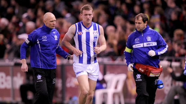 North Melbourne medical staff help an injured Lachie Hansen from the ground in round 20.