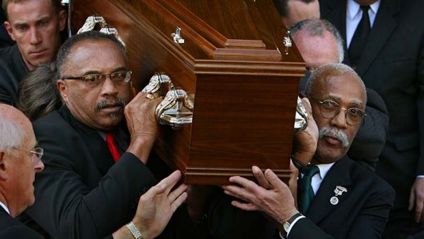 US athletes Tommie Smith,  left,  and John Carlos carry Peter Norman's coffin from the Williamstown Town Hall on  ...