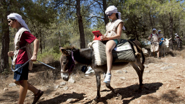 American tourist Ella uses an iPad while riding a wi-fi-outfitted donkey lead by her brother Aaron, in Kfar Kedem, a ...