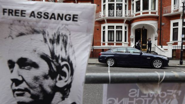 Shelter from the storm ... police stand guard outside the Ecuadorian embassy in London where Julian Assange is seeking ...