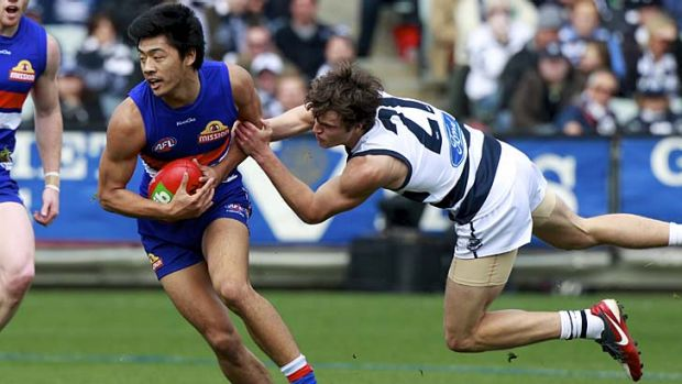 Western Bulldogs rookie Lin Jong shrugs off a tackle from Geelong's Jordan Murdoch.