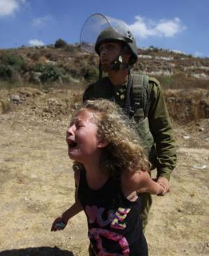An Israeli soldier restrains a Palestinian girl crying over the arrest of her mother   during a  protest over land ...
