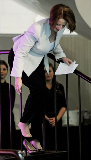 Prime Minister Julia Gillard places her foot back into her shoe after losing it walking on stage.