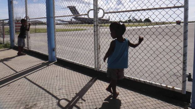 Nauruans watch a Royal Australian Air Force C-17 Globemaster III. The plane's arrival this week was a first step in ...
