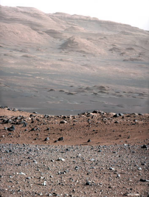 The gravelly area around Curiosity's landing site is visible in the foreground. Farther away, about a third of the way ...