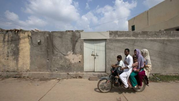 A family rides past the locked house of Rimsha Masih, a Pakistani Christian girl accused of blasphemy, on the outskirts ...