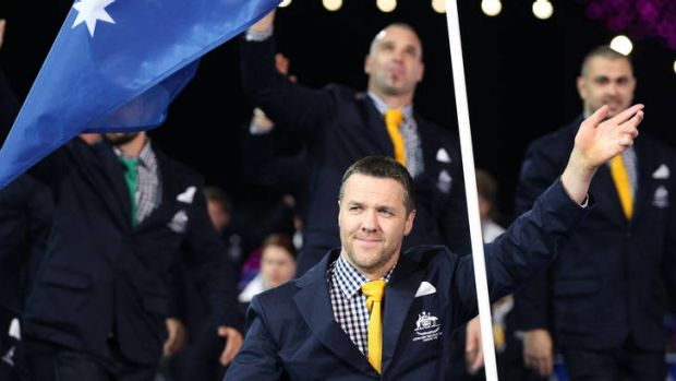 Wheelchair rugby player Greg Smith carries the flag for Australia.