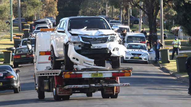 A tow truck removes the crashed ute from the scene of a double shooting in Sydney's west.