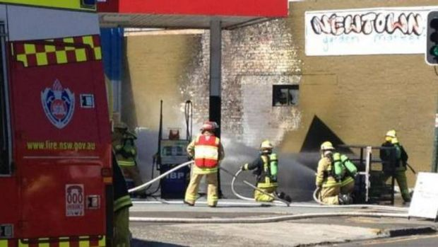 Firefighters stand by as gas bottles in a service station are doused with water to prevent an explosion on King Street.