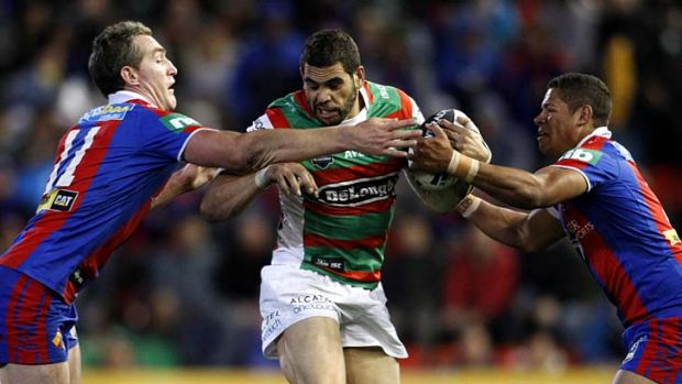 Double team ... Greg Inglis flanked by Newcastle's Chris Houston and Dane Gagai.