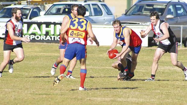 Purple patch: Unbeaten Violet Town's Tim Ross is about to handball to a teammate in a match against Nagambie.