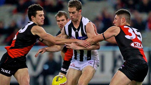 Two on one: Collingwood captain Nick Maxwell is put under pressure by young Bombers Jackson Merrett and Nick O'Brien at ...