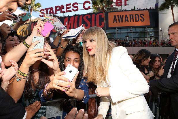Taylor Swift greets fans as she arrives at the awards.
