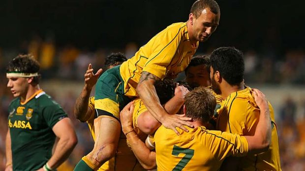 Jump for joy ... Quade Cooper joins fellow teammates to embrace Scott Higginbotham after his try brought the Wallabies ...