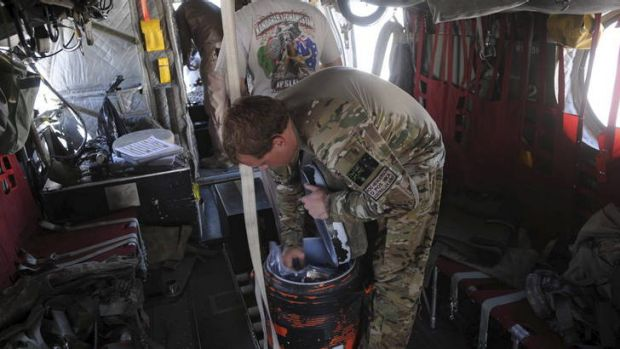 An Australian soldier reaches inside an esky in a Chinook Ch-47 D medium lift helicopter in Afghanistan.