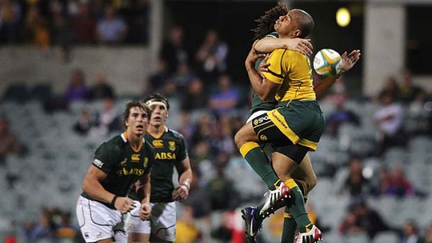 Bad break … South Africa's Zane Kirchner collides with Wallabies' captain Will Genia during the host's 26-19 win ...