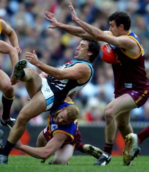 Port Adelaide's Roger James kicks into Brisbane's Nigel Lappin as he is dragged down by Michael Voss during the 2004 ...