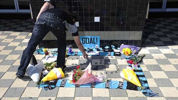 Port fan Vince Esposito places a candle at a makeshift shrine to John McCarthy outside the club's Adelaide headquarters.